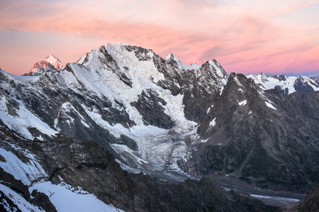 vertices: Sunundown in high snowy mountains. View of the glacier from the pass, a birds-eye view