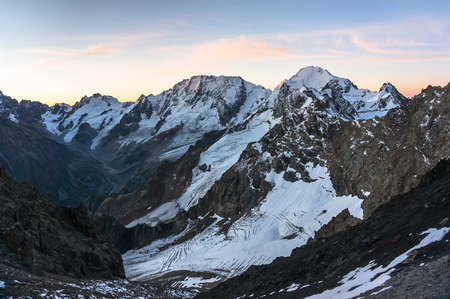 Evening in high snowy mountains. View of the glaciers from the pass, a bird's-eye view