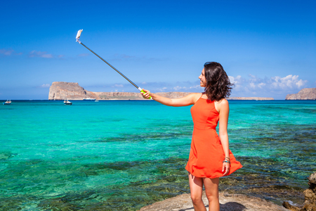 Pretty young woman dressed in a coral clothes having fun making selfie with a selfiestick on the background of the azure sea Imagens