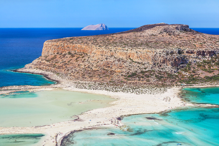 Scenic view of Balos bay on Crete island, Greece. Tourists relax and bath in crystal clear azure water of Balos beach.
