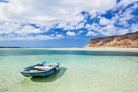 Romantic landscape with small wooden rowing boat in a beautiful bay with crystal clear water and the clouds in the sky. Balos bay on Crete island, Greece.