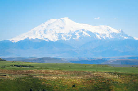 View of the highest mountain in Europe - Elbrus, 5642m. Located in Russia, Caucasus. Elbrus is of volcanic origin and has 2 summits. Huge snow-capped mountain towering over the green valley