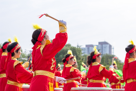 chinese drum: women are dressed in traditional red clothing to participate in traditional activities Editorial