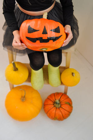 The little girl is holding a scary pumpkin for Halloween, sitting on a bench surrounded by other pumpkins. Closup 免版税图像