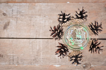 Beautiful Christmas and New Year decor, cones and lights garland in glass jar on wooden vintage background