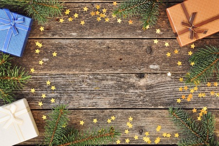 Holiday card for the new year is 2019 in warm, trendy colors. Christmas composition of spruce branches, gift, cinnamon, anise and confetti stars on rustic wooden background. Flat plan, top view.
