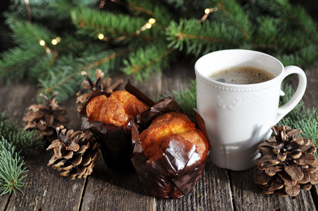 Christmas Breakfast of two cupcakes and a Cup of hot coffee on a wooden table, on the background of fir branches with lights 免版税图像