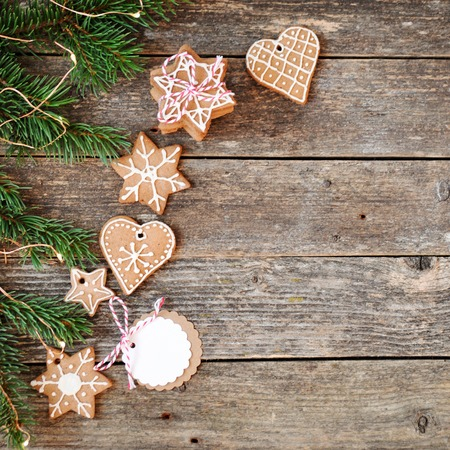 Merry christmas holiday decoration background.Traditional homemade Christmas gingerbread sugar frosting and gift box on a wooden background. Christmas tree decorated with lights. Copy space
