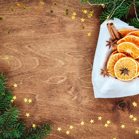 Holiday card for the new year is 2019 in warm, trendy colors. Christmas composition of ingredients for mulled wine cinnamon, orange slices, anise and confetti stars on rustic wooden background. Flat plan, top view. square Foto de archivo