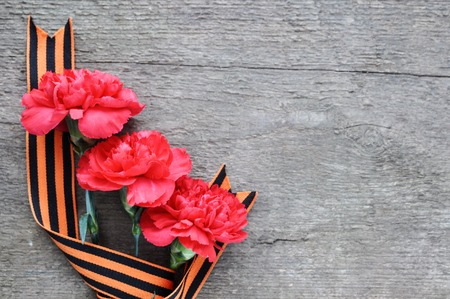 Bright holiday card on February 23. Red carnations on rustic wooden background. Fatherland defender day. The day of military glory.free space for text 写真素材