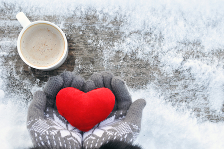 Valentine's day and Love frosty picture: a Cup of hot coffee on a wooden bench and hands in knitted gray gloves hold a plush red heart on a winter day. Valentine daytop view. copy spase