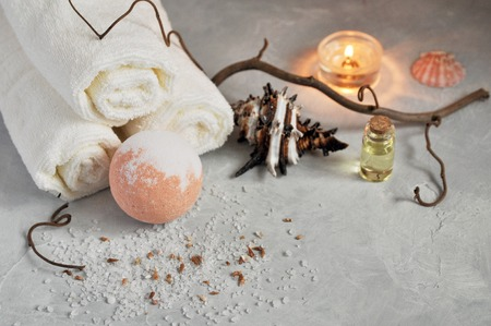 Spa relax concept. White Terry towels, stones, a candle and a bomb for a bath of sea salt on a gray textured background. Stockfoto