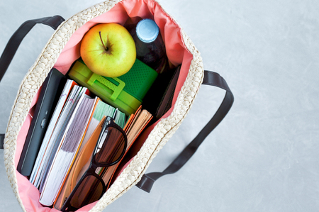 Stylish fashionable wicker bag with textbooks and notebooks, lunchbox and green Apple, water for a snack and sunglasses. Admission to University and summer session. Imagens