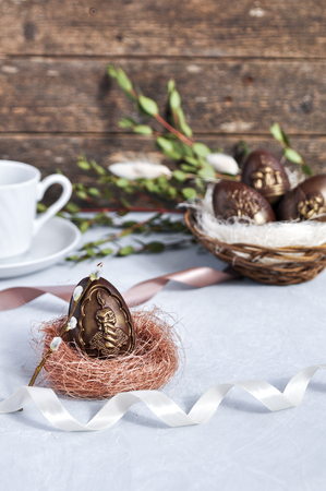 Handmade chocolate Easter eggs on a table decorated with satin ribbons, green branches and a Cup of coffee and a wooden background. Stok Fotoğraf - 122594499