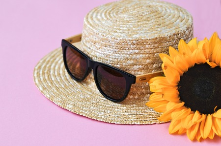 Summer straw hat, sunglasses and sunflower on pink background. close up. copy space