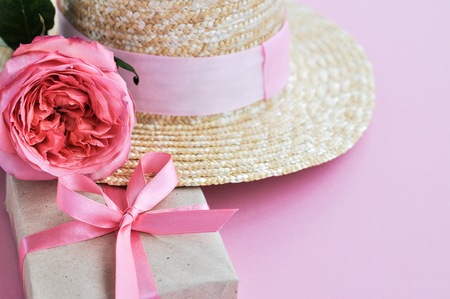 Delicate shabby card with Summer straw hat, pink peony rose and gift with bow on pink background. close up. copyspace Stock Photo