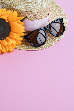 Summer straw hat, sunglasses and sunflower on pink background. close up. Foto de archivo