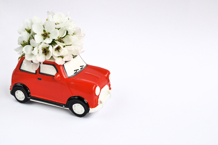 Red ceramic car with flowers on the roof on white background. February 14 card, Valentines day. Flower delivery. Stok Fotoğraf