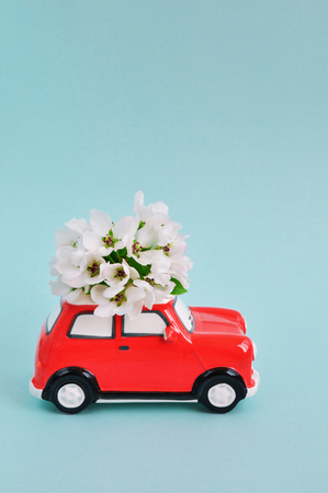 Red ceramic car with flowers on the roof on blue background. February 14 card, Valentines day. Flower delivery. 8 March, International Happy Womens Day. Copy spase Stok Fotoğraf
