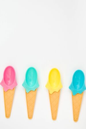 Summer bright ice cream spoons on white background.