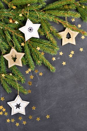 Christmas card with fir branches, wooden star decoration, gold confetti on dark background top view Standard-Bild