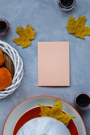 Halloween or Thanksgiving card on the table decorated with Pumpkin painted in white, orange plate and yellow leaves.