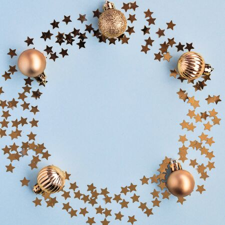 Christmas decor star confetti, gold balls in the shape of a circle on a blue background, mint. Top view, flat lay.
