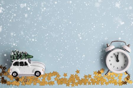 A cozy winter card with a Christmas car and a small alarm clock under the snow on a blue mint background. top view