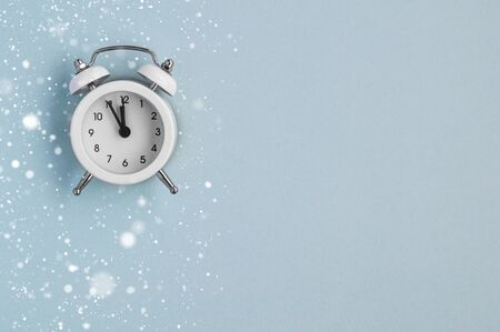 A cozy winter card with a small alarm clock under the snow on a blue mint background. top view Фото со стока