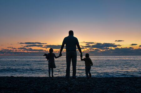 Dad with his daughter and son stand on the beach and looks at the waves in the rays of the sunset sea. silhouette
