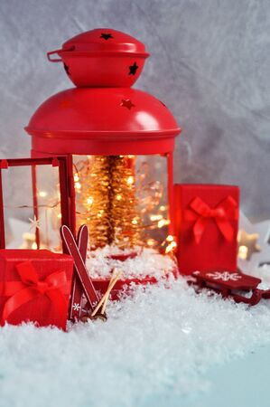 Christmas fairy composition of red lantern with Christmas tree and lights inside, decorative skis, sledges with decorations, gifts on snow on gray background.