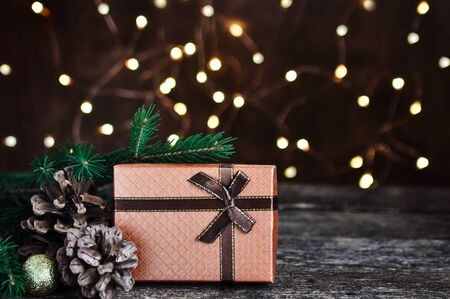 Holiday background with garland lights and trending bronze colors gift on wooden retro table.