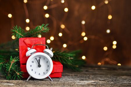 Christmas and new year background with garland lights and white alarm clock and red gifts on wooden retro table.
