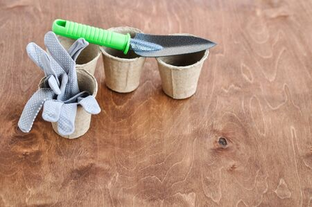 Grey reusable gardening gloves in a peat eco pot for seedlings and a metal shovel next to it on a brown wooden background. Reklamní fotografie