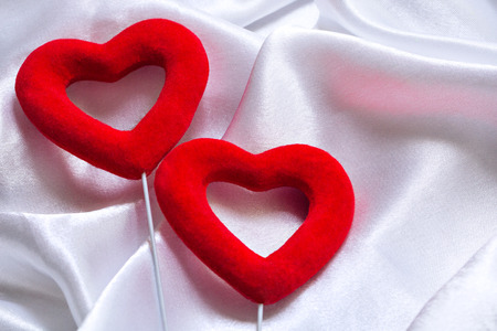 The concept of two lovers hearts lying on the white satin, can be used as a background, texture. Close Up
