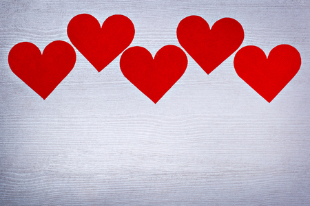 Five valentines hearts lined in a row on white wooden boards with place for text. Texture, background