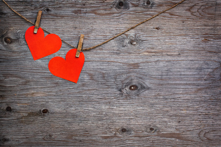 Two red paper hearts Valentines hanging on the rope on the clothespin. Wooden background texture Stock Photo