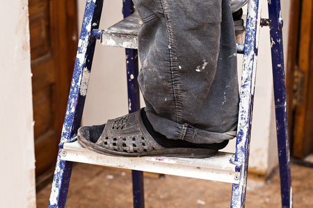 Foot of a builder on a ladder