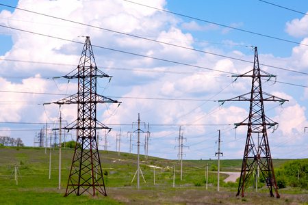 High voltage power line on a green field with blue sky and clouds
