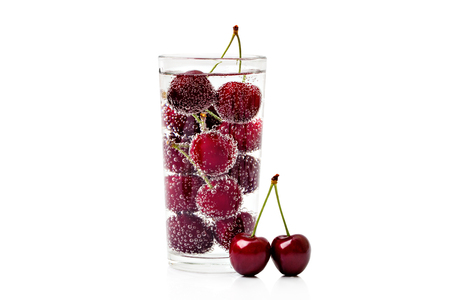 Cherries in a transparent glass with sparkling water isolated on white background