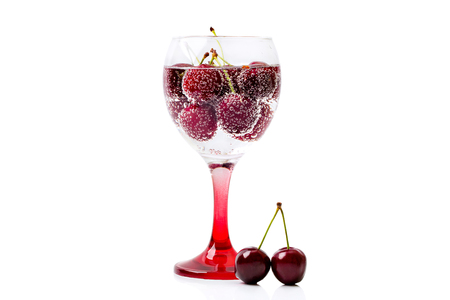 A glass of wine filled with sparkling water and berries of a ripe cherry isolated on a white background