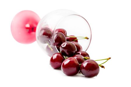 Cherries are poured from a wine glass. Isolated on white background