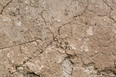 Cracked beige clay wall. Background. Texture