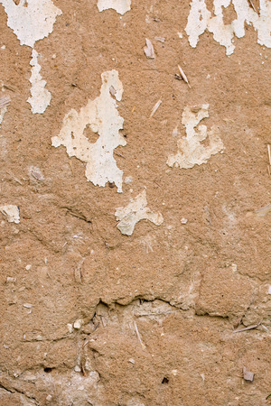 Cracked white paint on a wall of clay. Grunge wall of the old house, textured background
