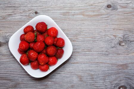 Strawberries berries in a white plate on a wooden background. Free copy space for text. Close up, top view
