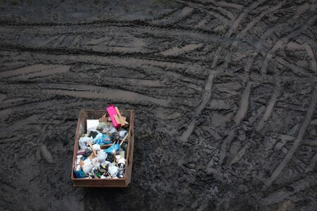 Trash in a large container, top view, dirt background