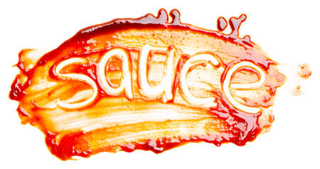 The word SAUCE written with finger on the spilled sauce isolated on white background. Top view, close up.
