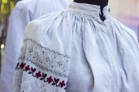 Old Ukrainian shirt embroidered linen with beautiful ornaments hanging on the mannequin, ethnic clothes