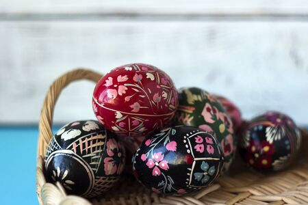 A lot of decorated Easter eggs lie in a basket, whte and blue background. Ukrainian Easter eggs with ornaments and patterns.