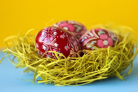 Three red decorated Easter eggs lie in a nest of hay on a yellow and blue background. Ukrainian Easter eggs with ornaments and patterns.